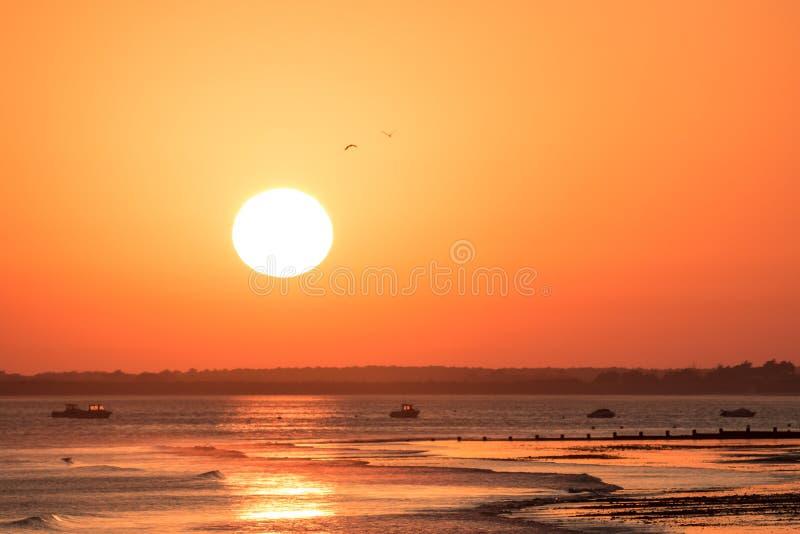 Caliente la puesta del sol anaranjada con el sol enorme en la costa costa de Océano Atlántico fotografía de archivo