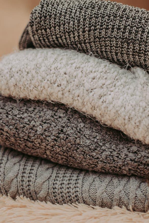 Caliente los suéteres hechos punto Pila de ropa hecha punto en fondo caliente, suéteres, géneros de punto, espacio para el texto imagenes de archivo