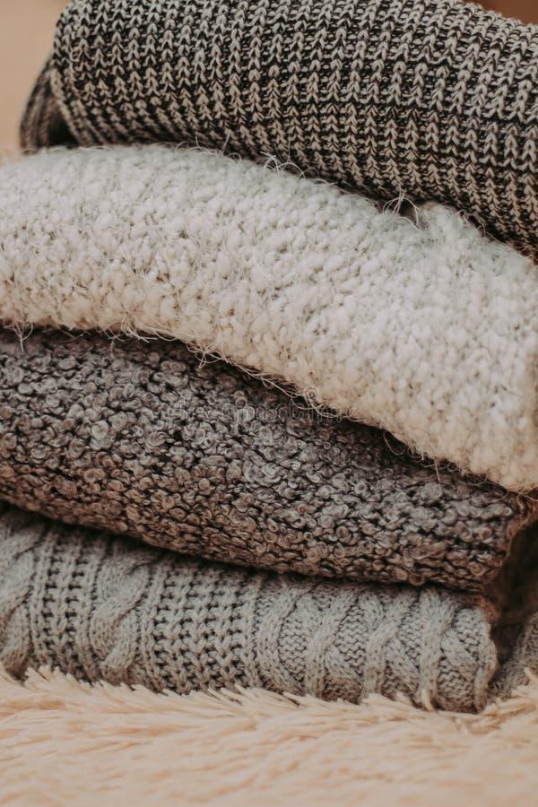 Caliente los suéteres hechos punto Pila de ropa hecha punto en fondo caliente, suéteres, géneros de punto, espacio para el texto foto de archivo
