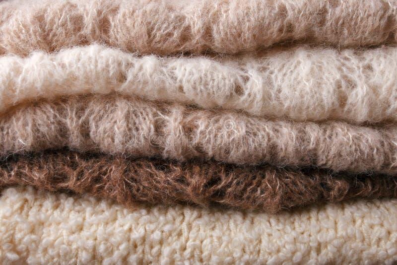 Caliente los suéteres hechos punto Pila de ropa hecha punto en fondo caliente, suéteres, géneros de punto, vertical, concepto del fotos de archivo