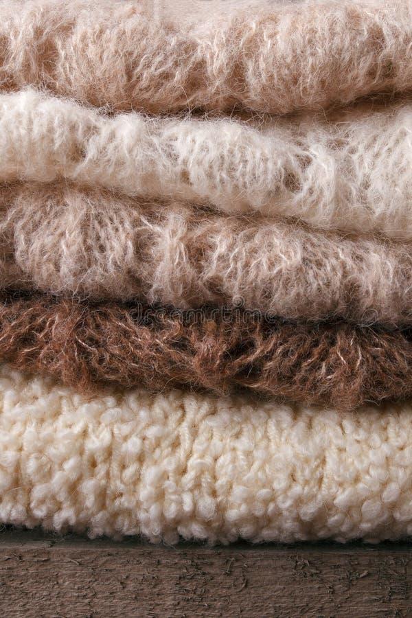 Caliente los suéteres hechos punto Pila de ropa hecha punto en fondo caliente, suéteres, géneros de punto, vertical, concepto del fotografía de archivo