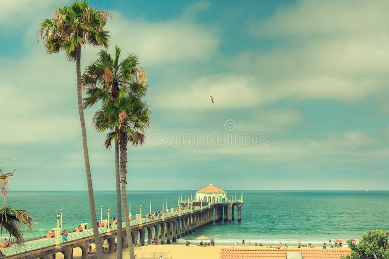 California beach. Palm trees on Manhattan Beach at sunset in California, Los Angeles, USA. Vintage processed. Fashion travel and tropical beach concept royalty free stock images