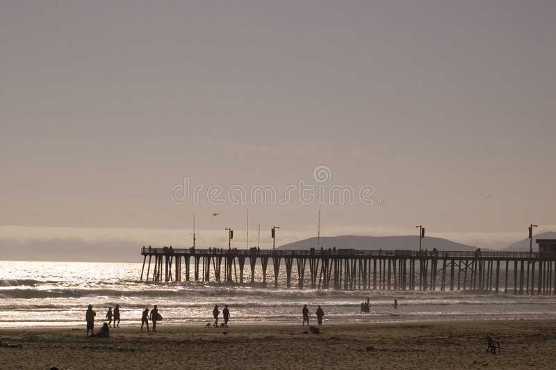 California beach at sunset. With pier and people playing royalty free stock images