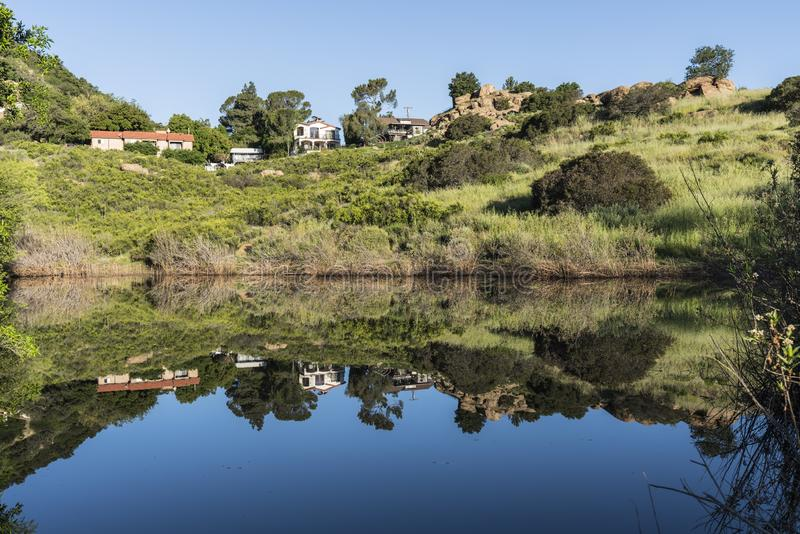 California Canyon Homes Reflecting in Spring Pond. Canyon homes and rock formations reflecting in spring fed mountain pond at Santa Susana Pass State Historic stock photo