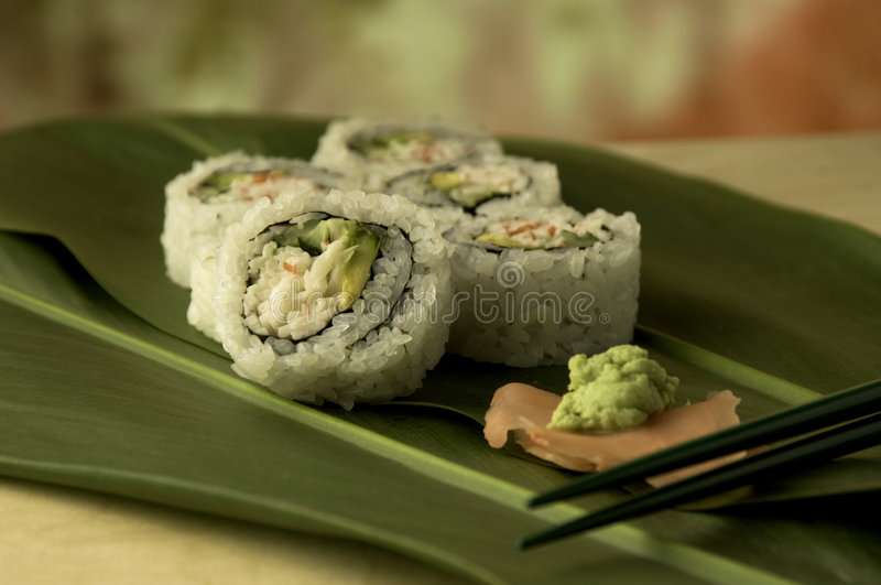 California Maki. A California Maki roll with wasabi and ginger on a bed of ti leafs stock photos