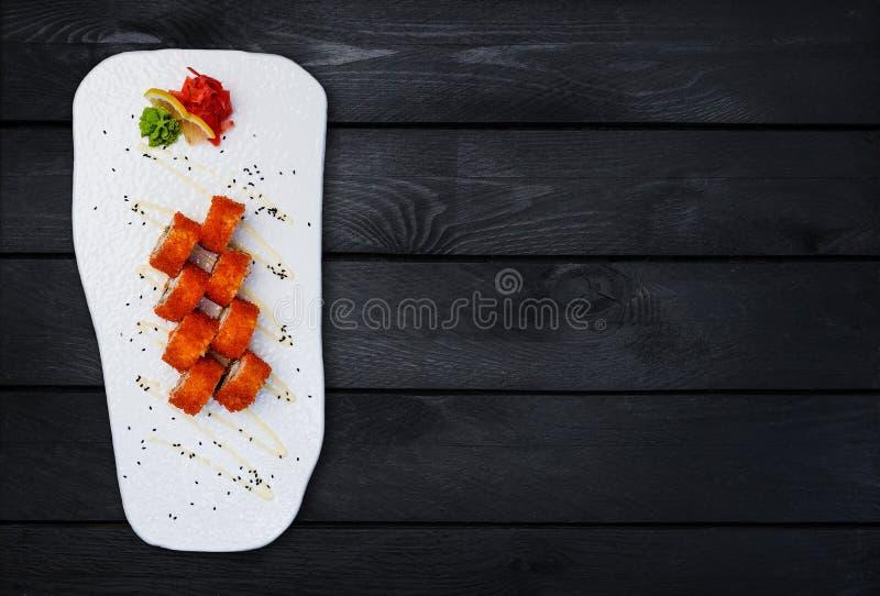 California Maki Sushi - rotolo fatto di polpa di granchio, avocado, cetriolo dentro Vista superiore Fondo di legno nero fotografia stock