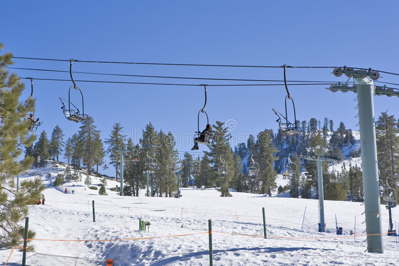 California Ski Resort Chair Lift. With Rider going up the Mountain royalty free stock photography