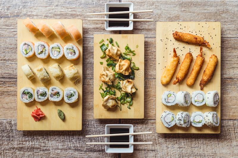 California sushi roll, sake sushi roll, fried shrimps, gyozas and soy sauce on a wooden table stock photo