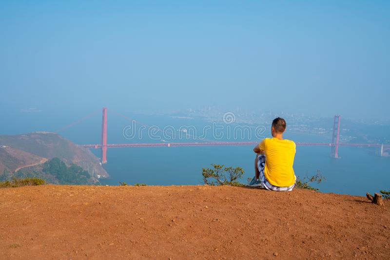 Young man walking on top of the hills with a Golden Gate bridge view in San Francisco. stock photos
