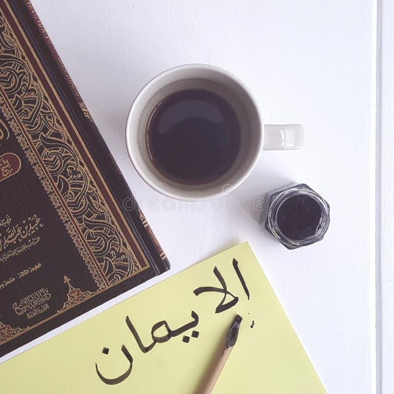 Caligrafia árabe Al Iman - fé na tabela com café e o livro islâmico foto imagem de stock royalty free