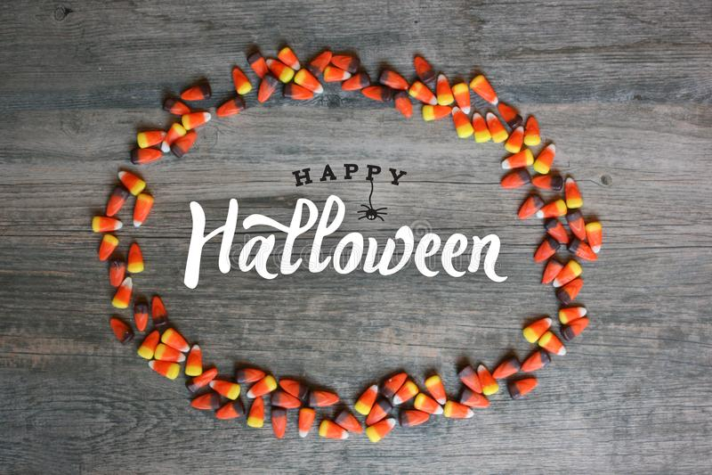 Caligrafia feliz de Dia das Bruxas com beira oval do milho de doces sobre o fundo de madeira rústico, horizontal fotografia de stock royalty free
