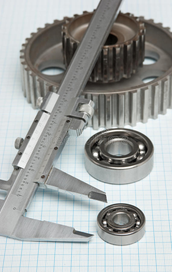 Caliper with gears and bearings. On graph paper royalty free stock photography