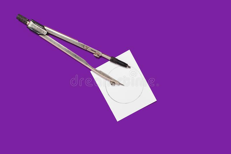 Calipers and a memorandum paper. Metal calipers and a memorandum white paper lying on a purple background . concept of office chancery. free space for royalty free stock photos