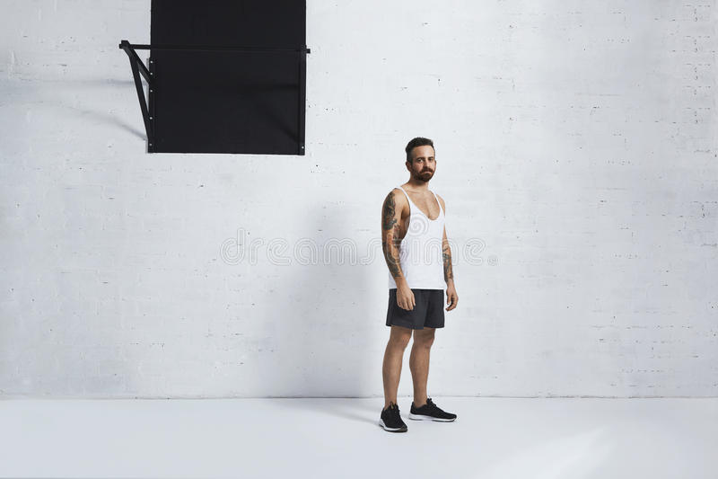 Calisthenic and bodyweight exercises. Athletic brutal and tattooed young man in plain blank tank t-shirt standing near to pull-up bar in front of grunge brick royalty free stock image