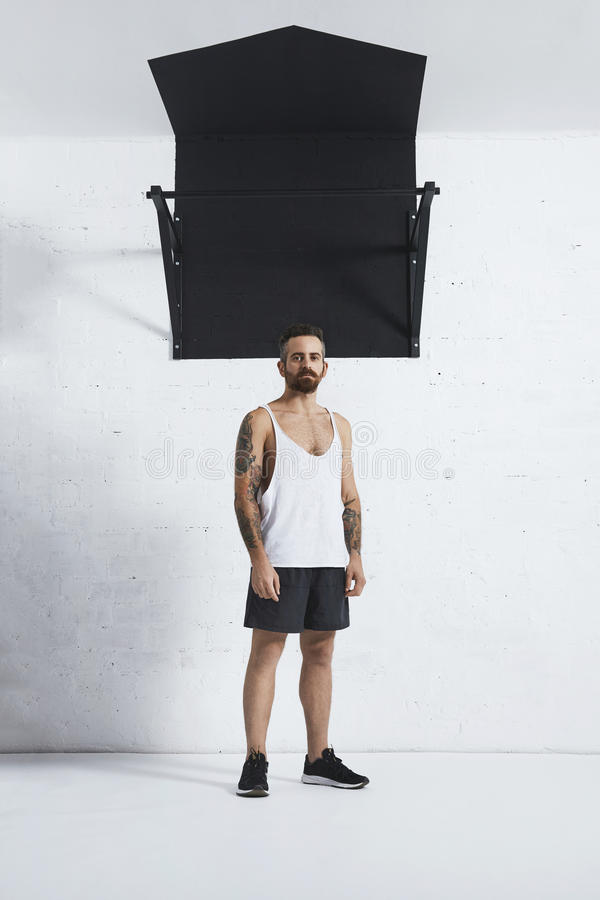 Calisthenic and bodyweight exercises. Athletic brutal and tattooed young man standing next to pull-up bar in front of grunge brick wall in white gym stock photos