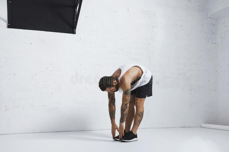Calisthenic and bodyweight exercises. Athletic tattooed man in white blank tank t-shirt stretching his legs touching them on the floor, left side position royalty free stock photos