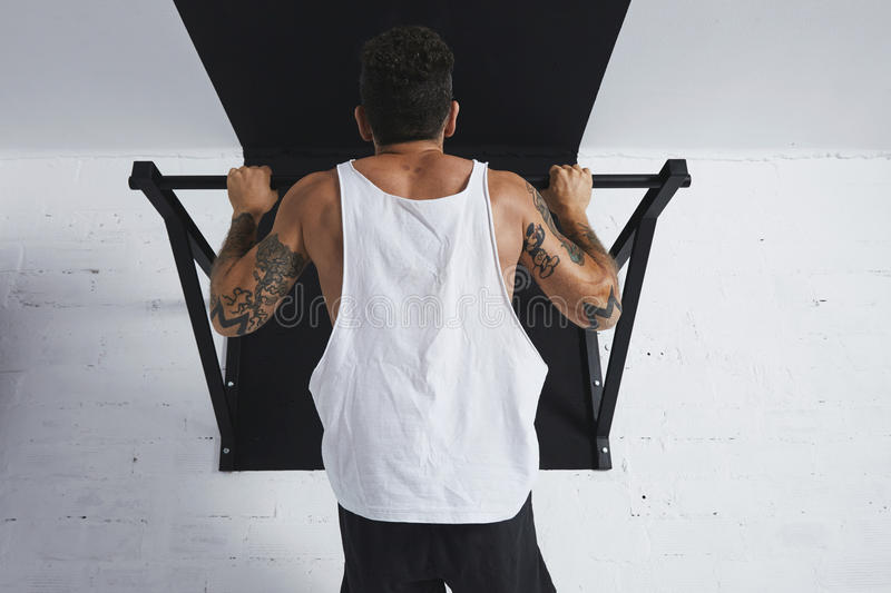 Calisthenic and bodyweight exercises. Back view on muscular male athlete in white blank tank t-shirt showing calisthenic moves Pull up on pullbar, holding on top royalty free stock photography
