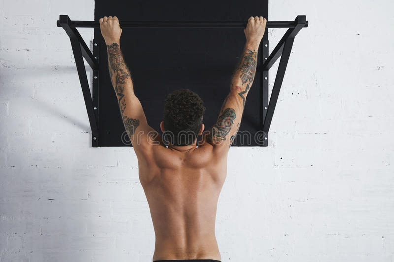 Calisthenic and bodyweight exercises. Back view on muscular topless male athlete showing calisthenic moves Hanging on pullbar royalty free stock image