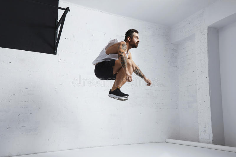 Calisthenic and bodyweight exercises. Bearded and tattooed young male athlete shows calisthenic moves, jumping high in air, in white room of fitness center royalty free stock photography