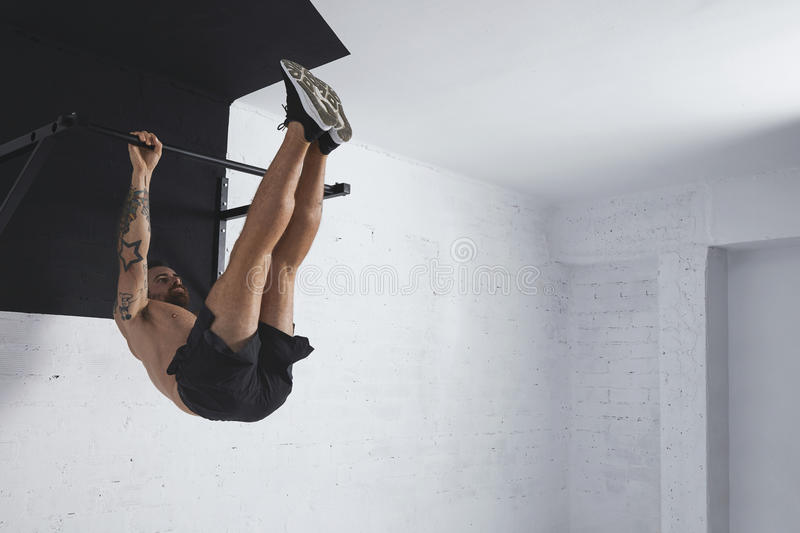 Calisthenic and bodyweight exercises. Strong tattooed athlete shows how to do calisthenic moves step by step Full leg rises on pull bar royalty free stock photo