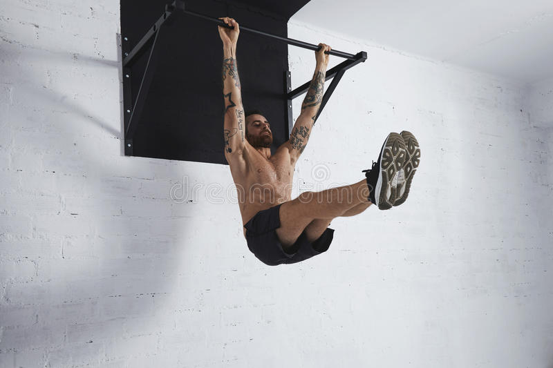 Calisthenic and bodyweight exercises. Strong tattooed athlete shows how to do calisthenic moves step by step Full leg rises on pull bar medium position stock photography
