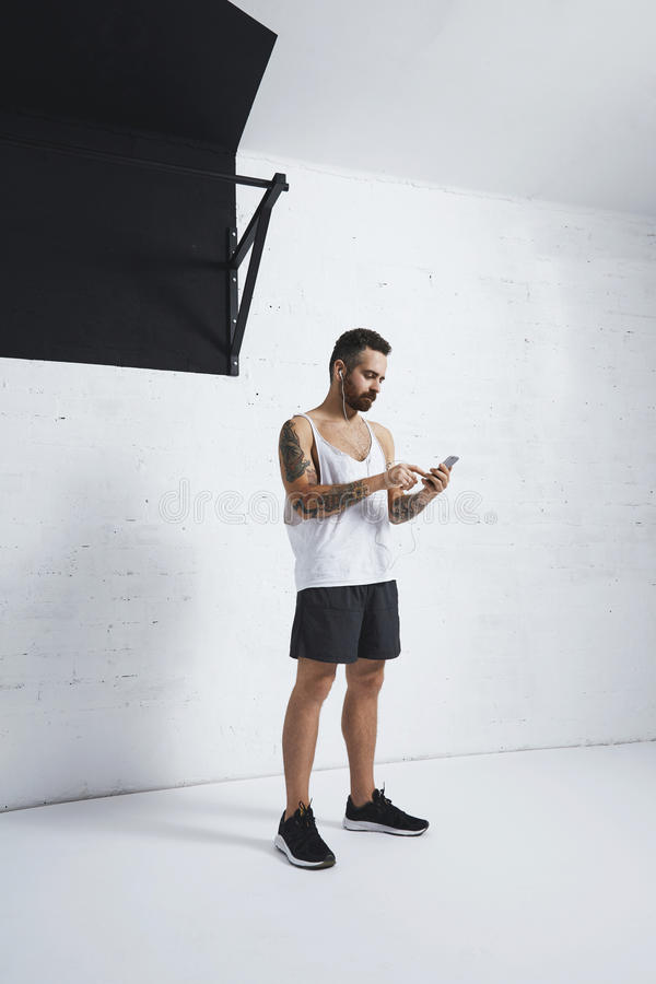 Calisthenic and bodyweight exercises. Strong tattooed athlete with smartphone and earbuds taps screen with his finger, standing next to pull bar in white gym royalty free stock image