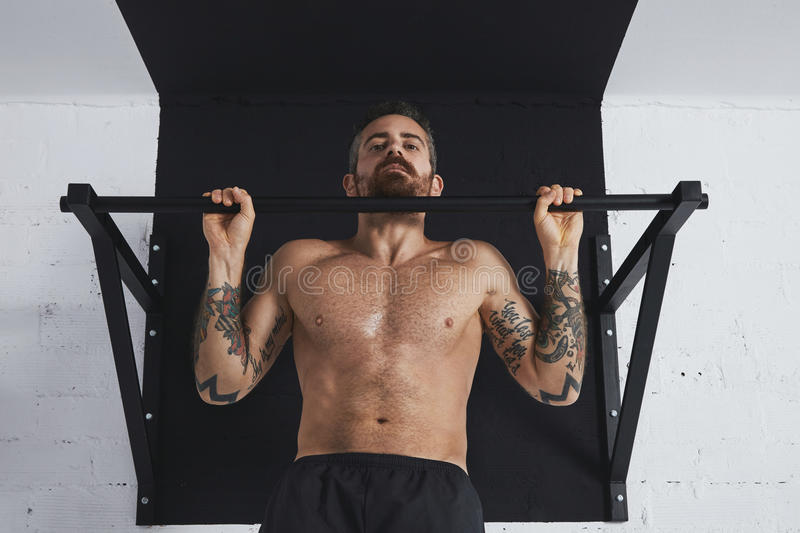 Calisthenic and bodyweight exercises. Strong tattooed topless male athlete shows calisthenic moves close up of classic pullup hold in top bar stock images