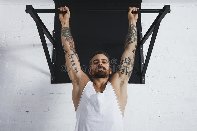 Calisthenic and bodyweight exercises. Strong tattooed in white unlabeled tank t-shirt male athlete shows calisthenic moves close up of classic pullup Hanging on stock photography