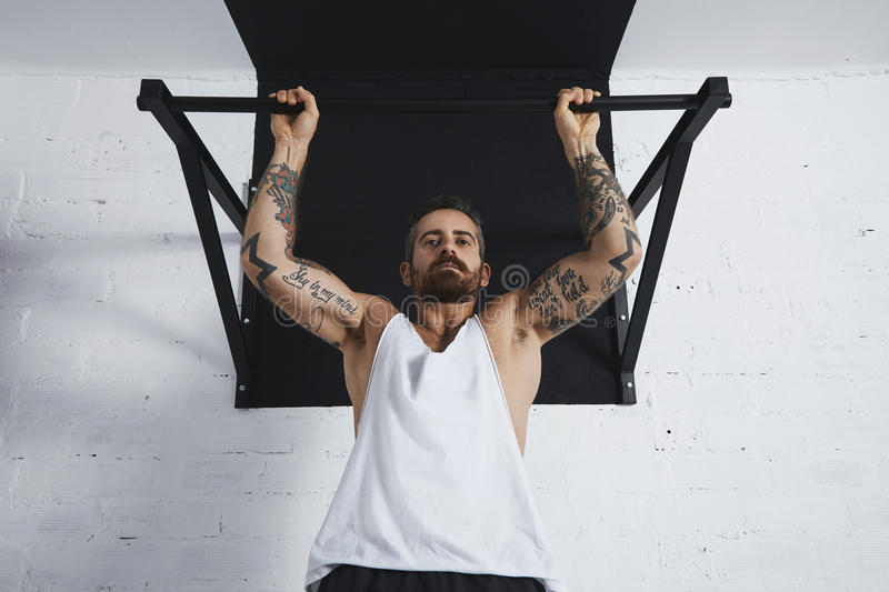 Calisthenic and bodyweight exercises. Strong tattooed in white unlabeled tank t-shirt male athlete shows calisthenic moves close up Pullup hold on medium move on stock photos