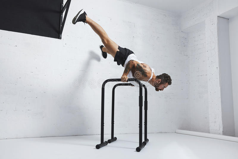 Calisthenic and bodyweight exercises. Strong tattooed in white unlabeled tank t-shirt male athlete shows calisthenic moves Extended legs planche push ups on royalty free stock images