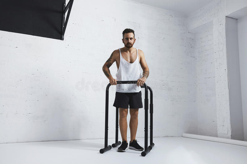 Calisthenic and bodyweight exercises. Strong tattooed in white unlabeled tank t-shirt male athlete shows calisthenic moves Extended legs plance push ups on stock photo