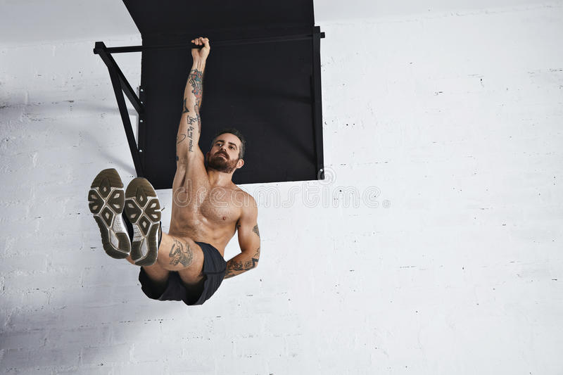 Calisthenic and bodyweight exercises. Strong tattooed in white unlabeled tank t-shirt male athlete shows calisthenic moves Hanging on pull bar one arm leg raises royalty free stock image