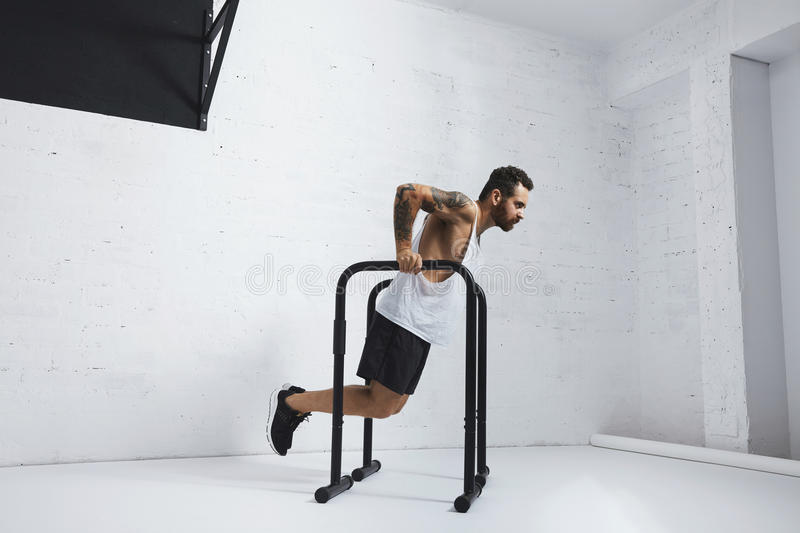 Calisthenic and bodyweight exercises. Strong tattooed in white unlabeled tank t-shirt male athlete shows calisthenic moves Holding dip position on parallel bars stock image
