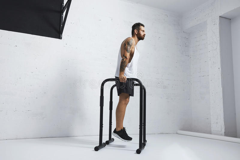 Calisthenic and bodyweight exercises. Strong tattooed in white unlabeled tank t-shirt male athlete shows calisthenic moves Holding position on parallel bars royalty free stock photo