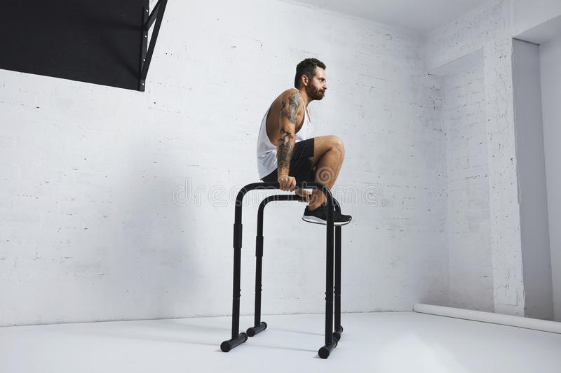 Calisthenic and bodyweight exercises. Strong tattooed in white unlabeled tank t-shirt male athlete shows calisthenic moves Kick out L Sit move or tucked on stock image