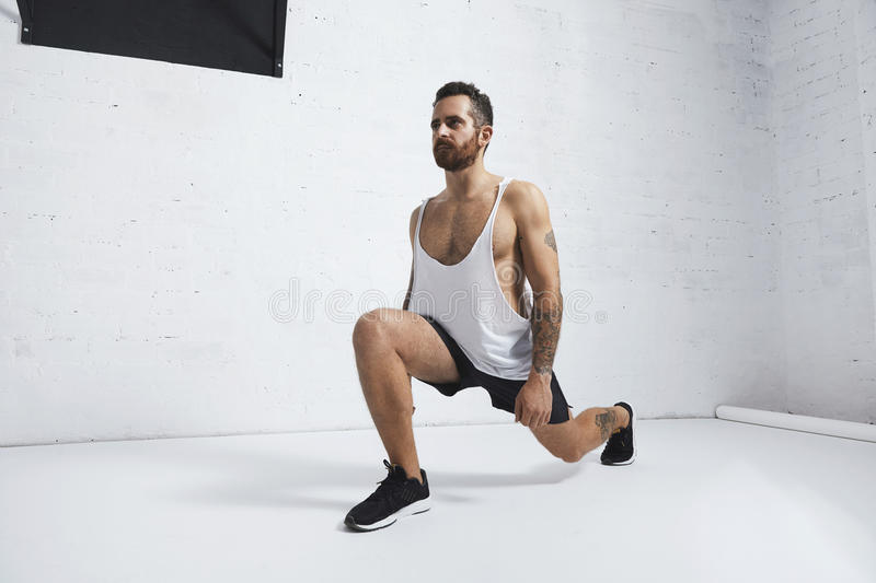 Calisthenic and bodyweight exercises. Strong tattooed in white unlabeled tank t-shirt male athlete shows calisthenic moves Lunges, looking on side royalty free stock photos