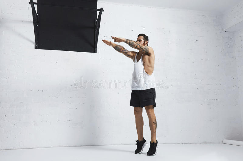 Calisthenic and bodyweight exercises. Strong tattooed in white unlabeled tank t-shirt male athlete shows calisthenic moves Squat calf rises, top position stock image