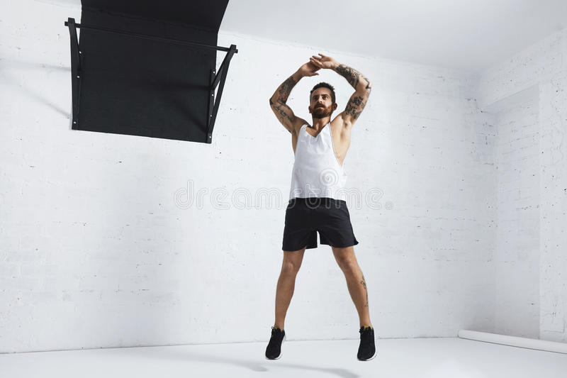 Calisthenic and bodyweight exercises. Tattooed and muscular athlete doing jumping jacks on white brick wall next to black pull bar royalty free stock photos