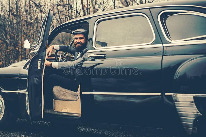 Call boy in vintage auto. Bearded man in car. Retro collection car and auto repair by mechanic driver. Travel and stock photo