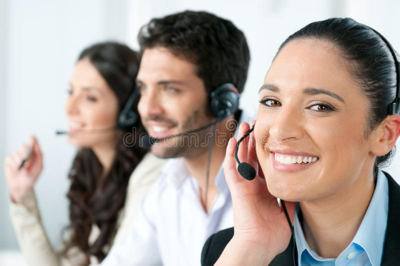 Call center. Beautiful young lady talking on headset at call center office