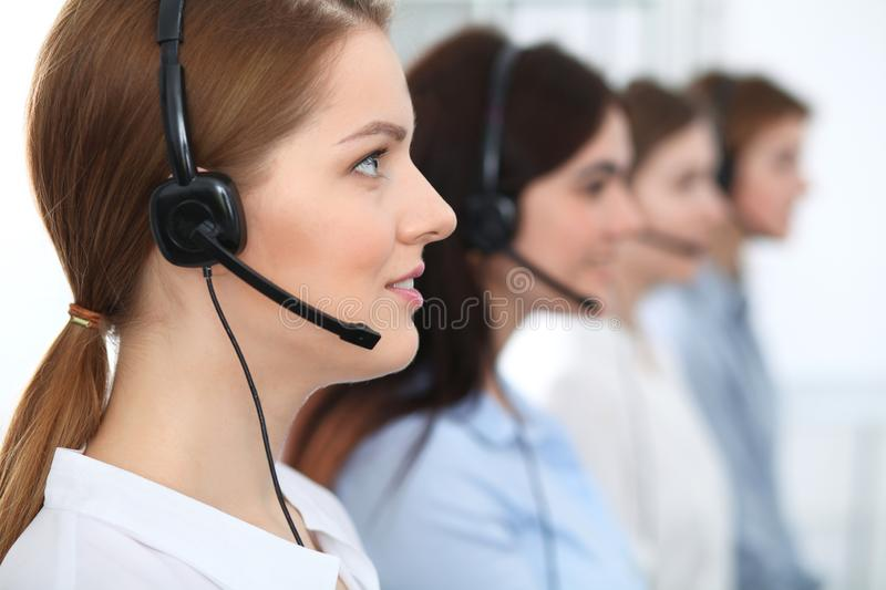 Call center. Beautiful cheerful smiling operator consulting clients with headset. Business concept of customer service royalty free stock photo
