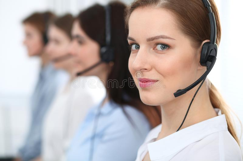 Call center. Beautiful cheerful smiling operator consulting clients with headset. Business concept of customer service royalty free stock image