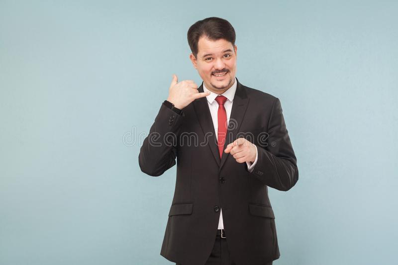 Call center. Businessman showing phone sign. And smiling. indoor studio shot. isolated on light blue background. handsome businessman with black suit, red tie royalty free stock image