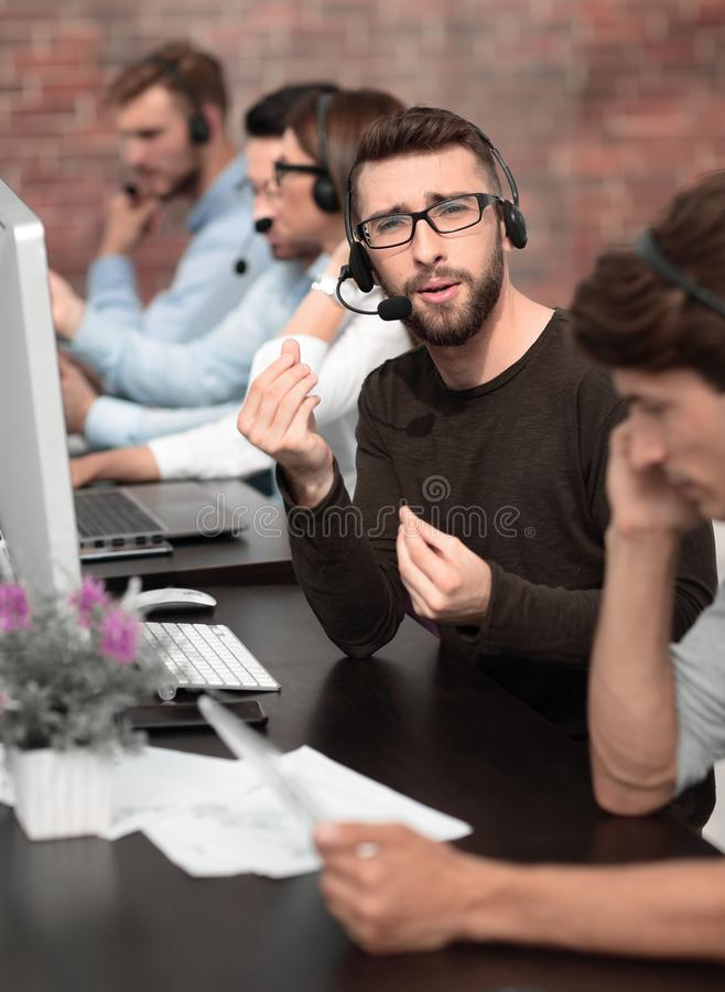 Call center employee explains something sitting at the table royalty free stock images