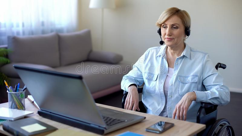 Call-center female operator in headphones talking with client, disabled woman stock images