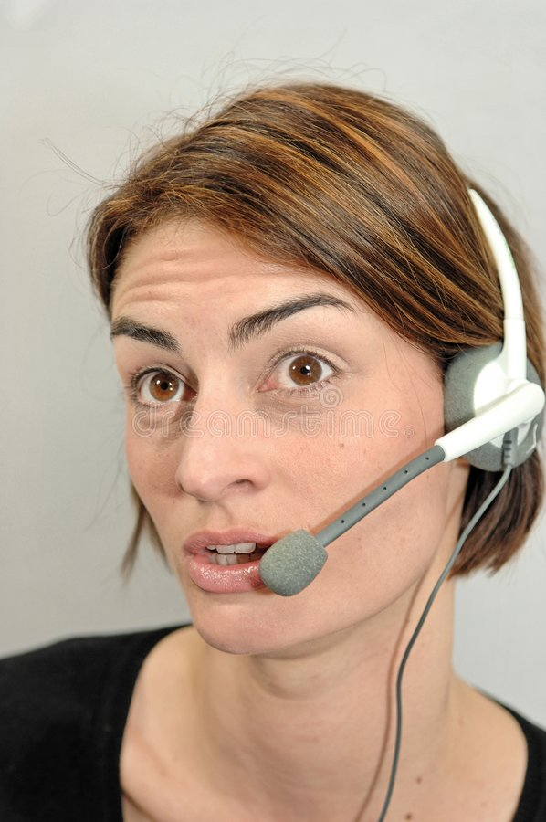 Call center girl looks amazed. A young women talking via headphone stock images