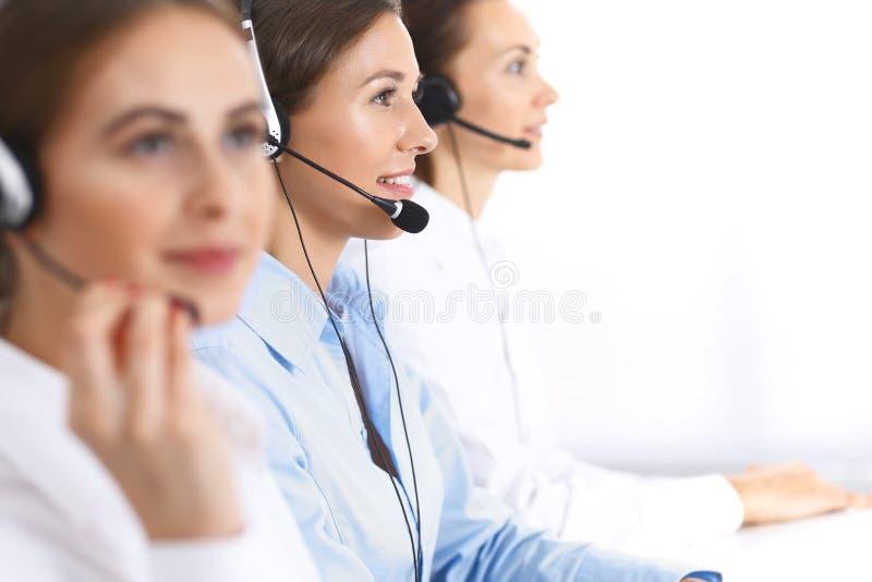 Call center Gruppo di operatori sul lavoro Fuoco sulla bella donna di affari in cuffia avricolare fotografia stock