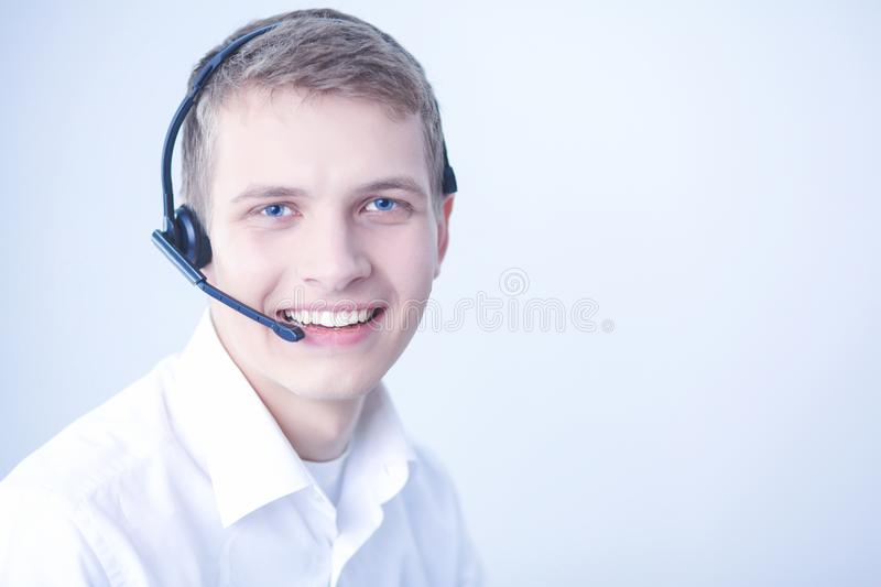 Customer support operator with a headset on white background. Call center male operator on gray background stock photos