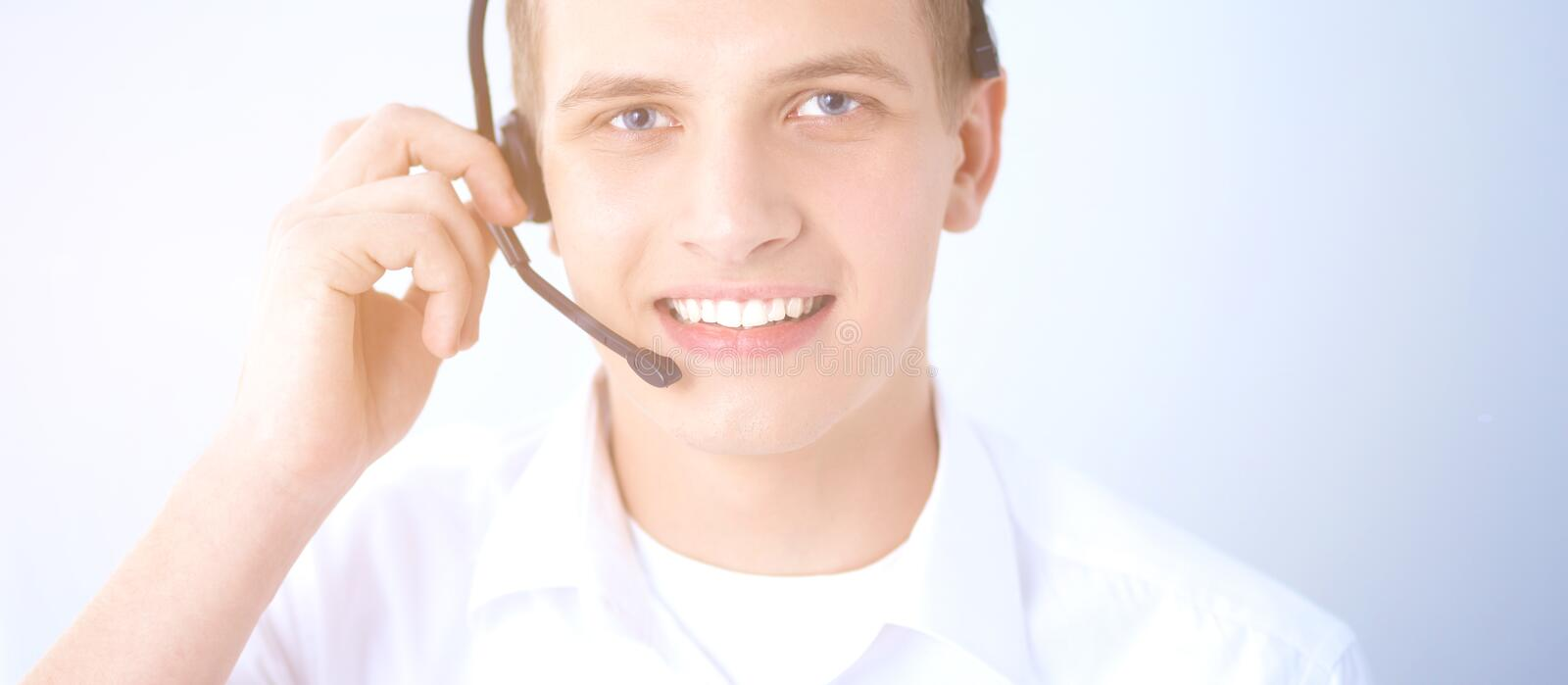 Customer support operator with a headset on white background. Call center male operator on gray background royalty free stock photos