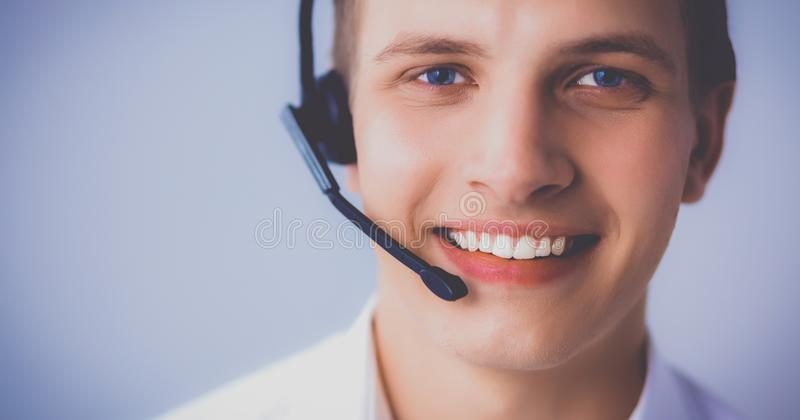 Customer support operator with a headset on white background. Call center male operator on gray background royalty free stock images